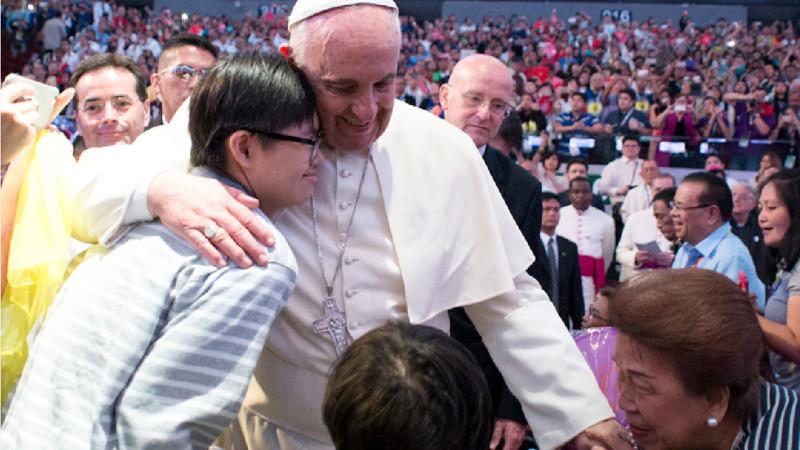 Papst Franziskus umarmt einen Jugendlichen  | © KNA.