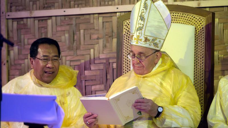 Papst Franziskus in einem gelben Regencape bei einem Freiluftgottesdienst in Tacloban am 17. Januar | © 2015 KNA
