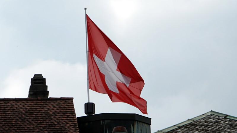 Schweizer Fahne über Hausdächern   | © 2015 Georges Scherrer