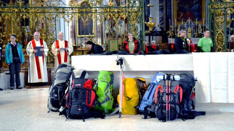 Frauen Pilgern nach Rom – Rucksäcke der Pilger am Altar, im Hintergrund v.l.n.r.: Hildegard Aepli, Markus Büchel, Martin Gächter | © 2016 Sylvia Stam