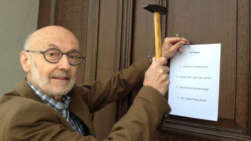 Josef Hochstrasser nagelt seine Thesen an eine Kirchentür | © Veronica Hunziker