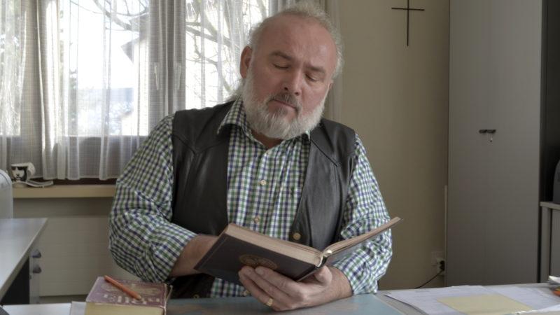 Josip Knezevic mit Koran und Bibel im Pfarreibüro in Rüschlikon ZH  | © Regula Pfeifer