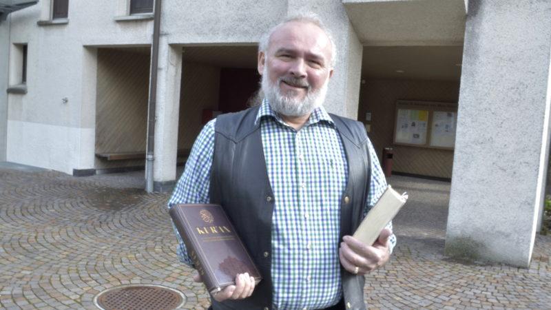 Josip Knezevic mit Koran und Bibel vor dem katholischen Pfarreizentrum Rüschlikon ZH  | © Regula Pfeifer