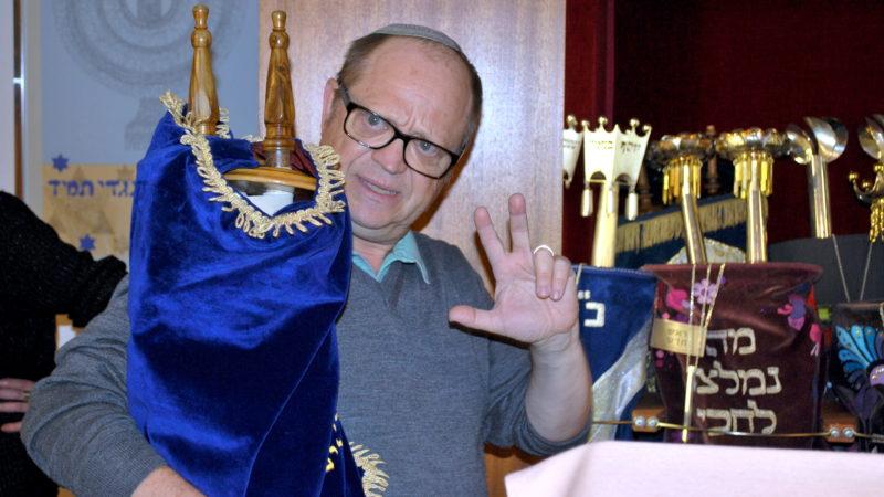 Michel Bollag mit einer Thorarolle im Arm, im Hintergrund der geöffnete Thoraschrein im Minjan Wollishofen | © Barbara Ludwig