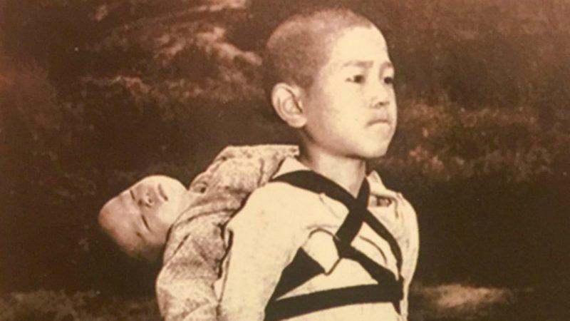 Der Knabe von Nagasaki trägt seinen toten Bruder zur Leichenverbrennung. |  © Joseph Roger O'Donnell, 1945