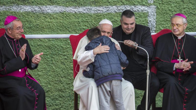 Papst Franziskus umarmt einen Jungen. | © KNA