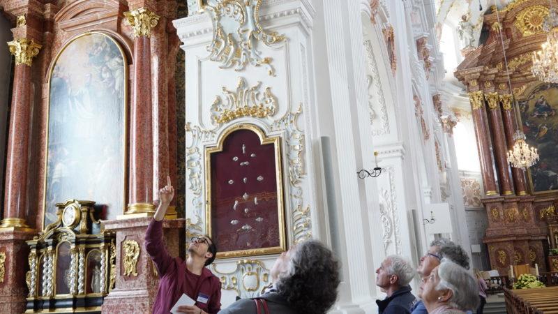 Ein Living Stones-Guide mit einer Gruppe in der Jesuitenkirche | © Vera Rüttimann