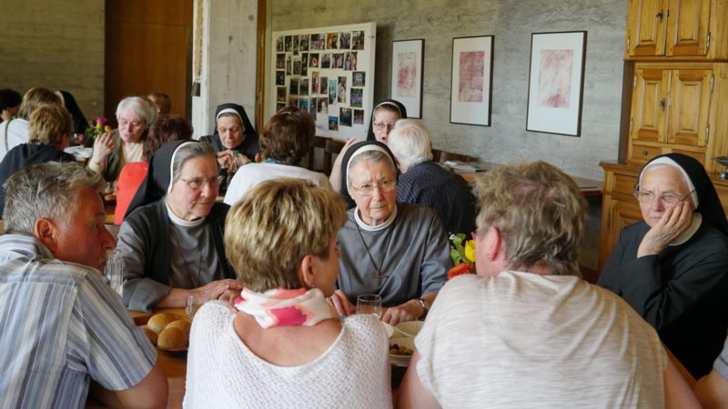 Schwestern mit Gästen am Tisch im Kloster | © Vera Rüttimann