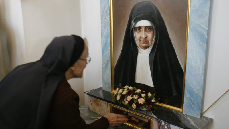 Pilgerin berührt Reliquium der Heiligen Maria Bernarda in der Pfarrkirche von Auw  | © keystone