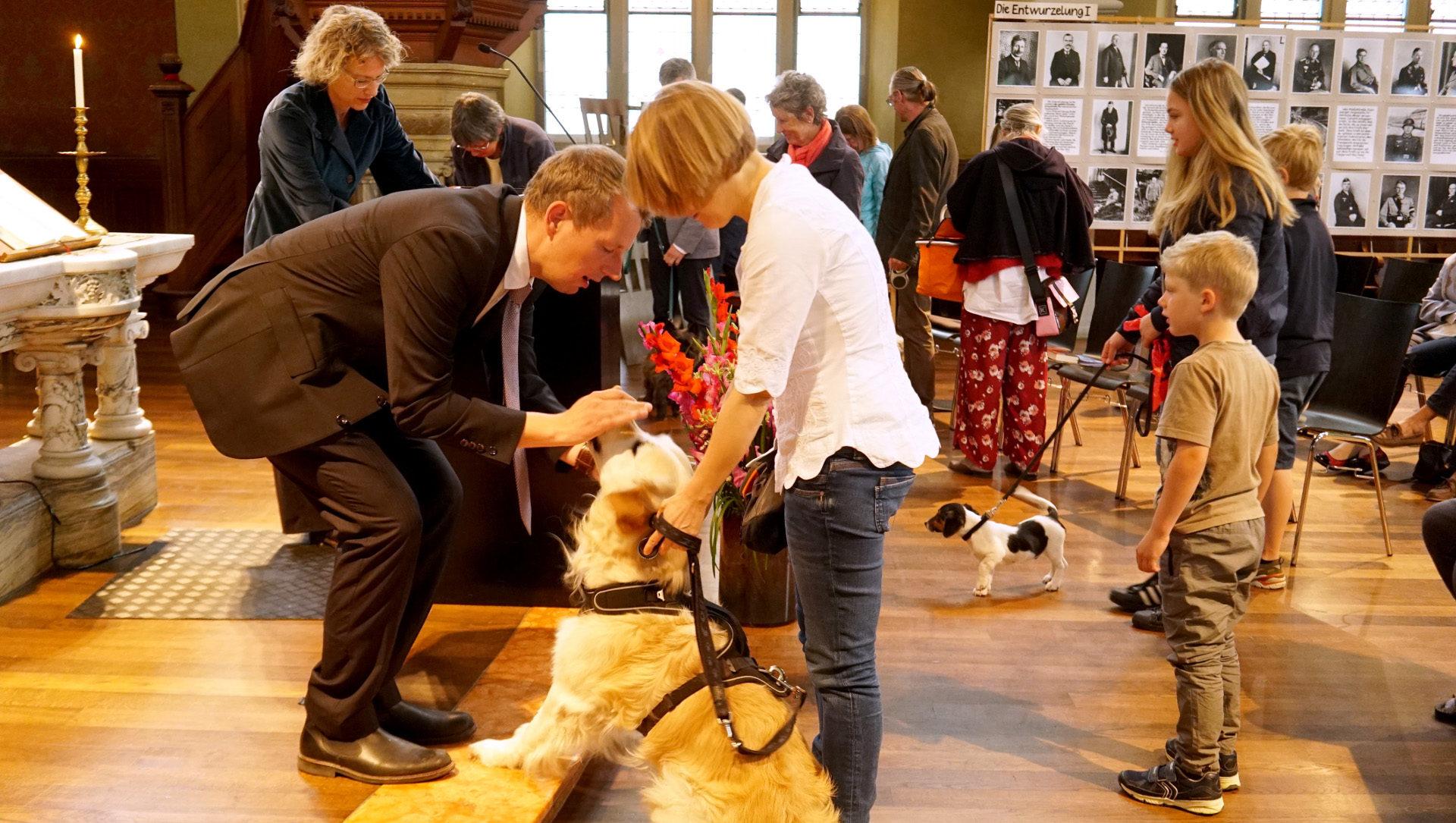 Pfarrer Michael Schaar segnet einen Hund | © Vera Rüttimann