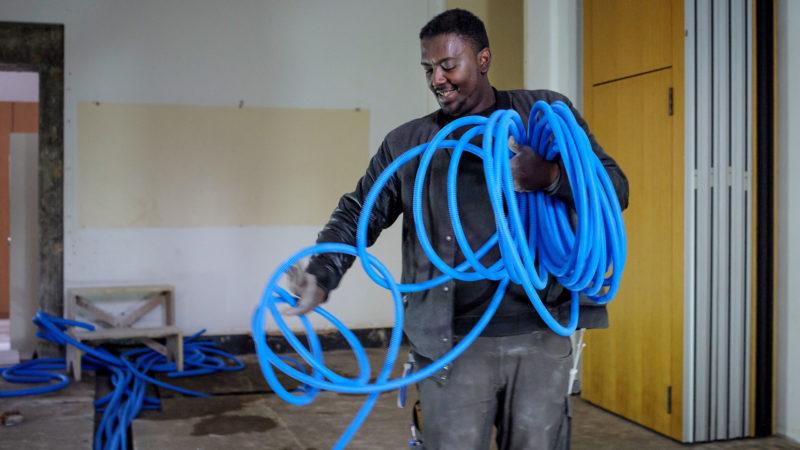 Beispiel aus der Integrationsarbeit von Caritas Freiburg: Ein Migrant aus Eritrea arbeitet als Elektromonteur-Lehrling. | © Flurin Bertschinger/Ex-Press/Caritas