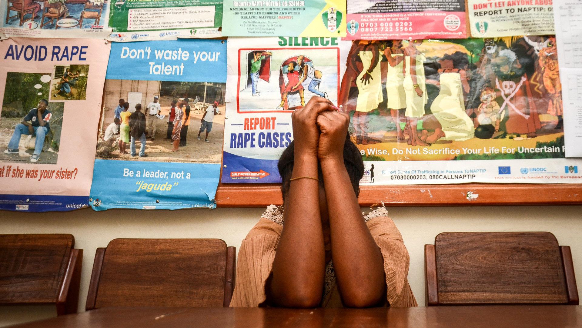 Eine Frau vor Plakaten, die vor Vergewaltigung, Menschenhandel und Zwangsprostitution warnen. | © KNA