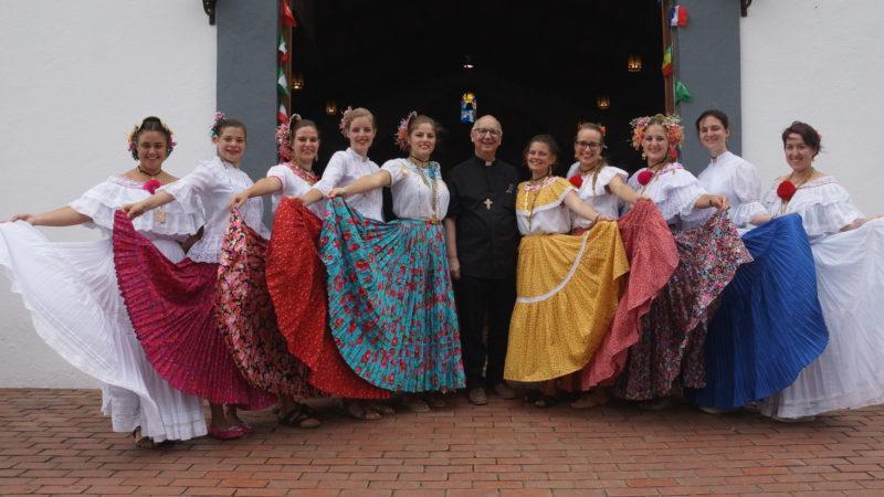 Bischof Marian Eleganti am Weltjugendtag mit festlich gekleideten jungen Frauen. | zVg