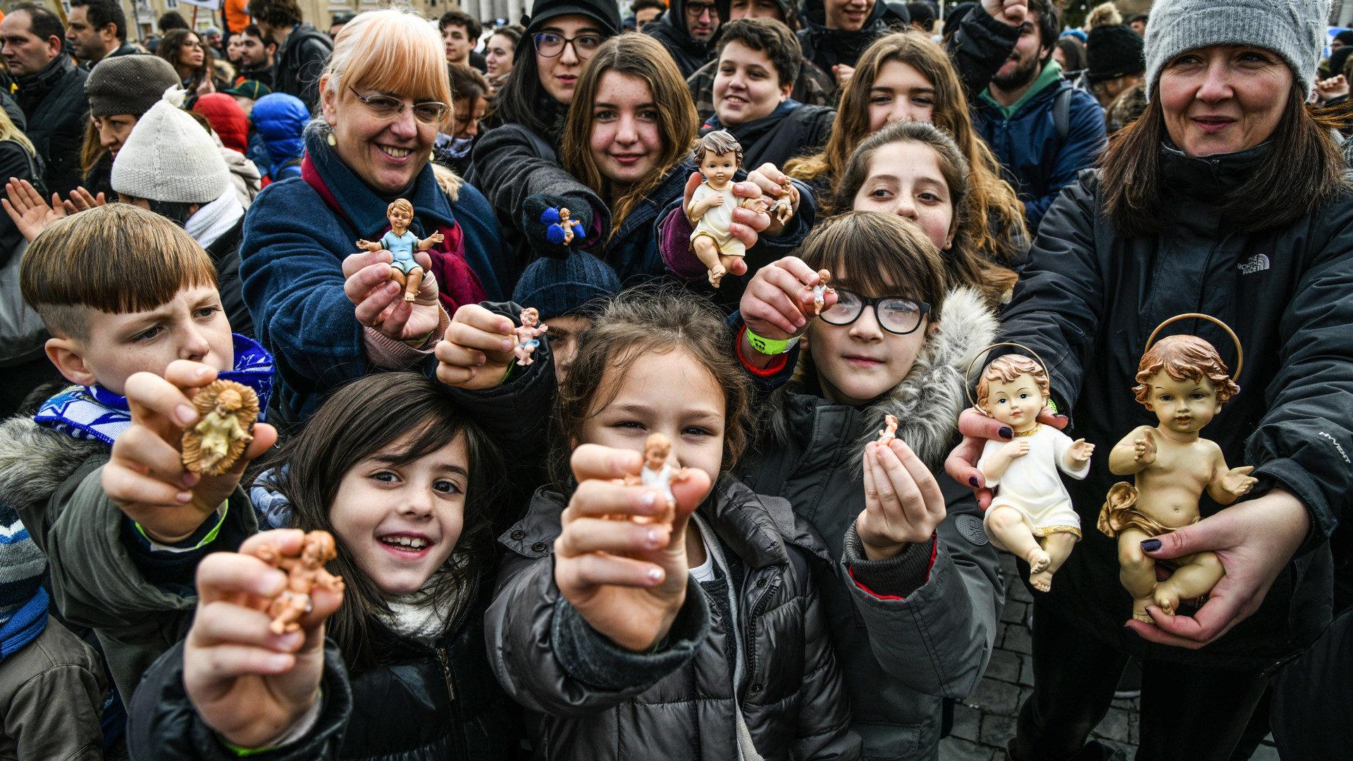 Kinder und Erwachsene halten auf dem Petersplatz Figuren von Jesuskindern vor sich.   © KNA