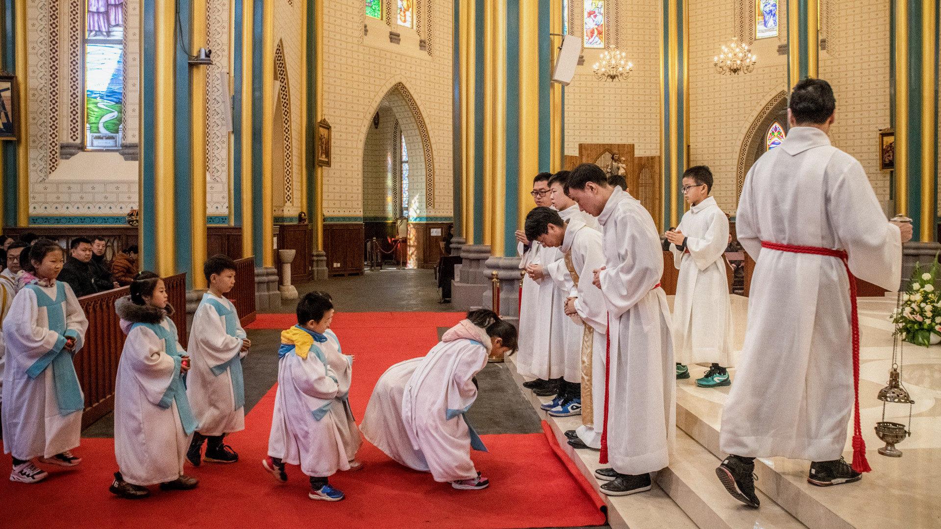 Kinder verbeugen sich vor dem Priester während einer Messe  in Peking.   © KNA