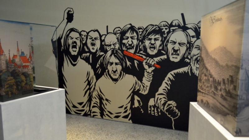Ein Mob geht auf ein Opfer los. Wandbild in der «Sündenbock»-Ausstellung | © Regula Pfeifer