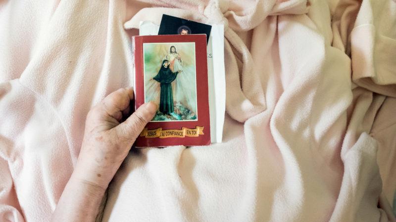 Patientin einer Palliativstation mit Heiligenbildern in der Hand | © KNA