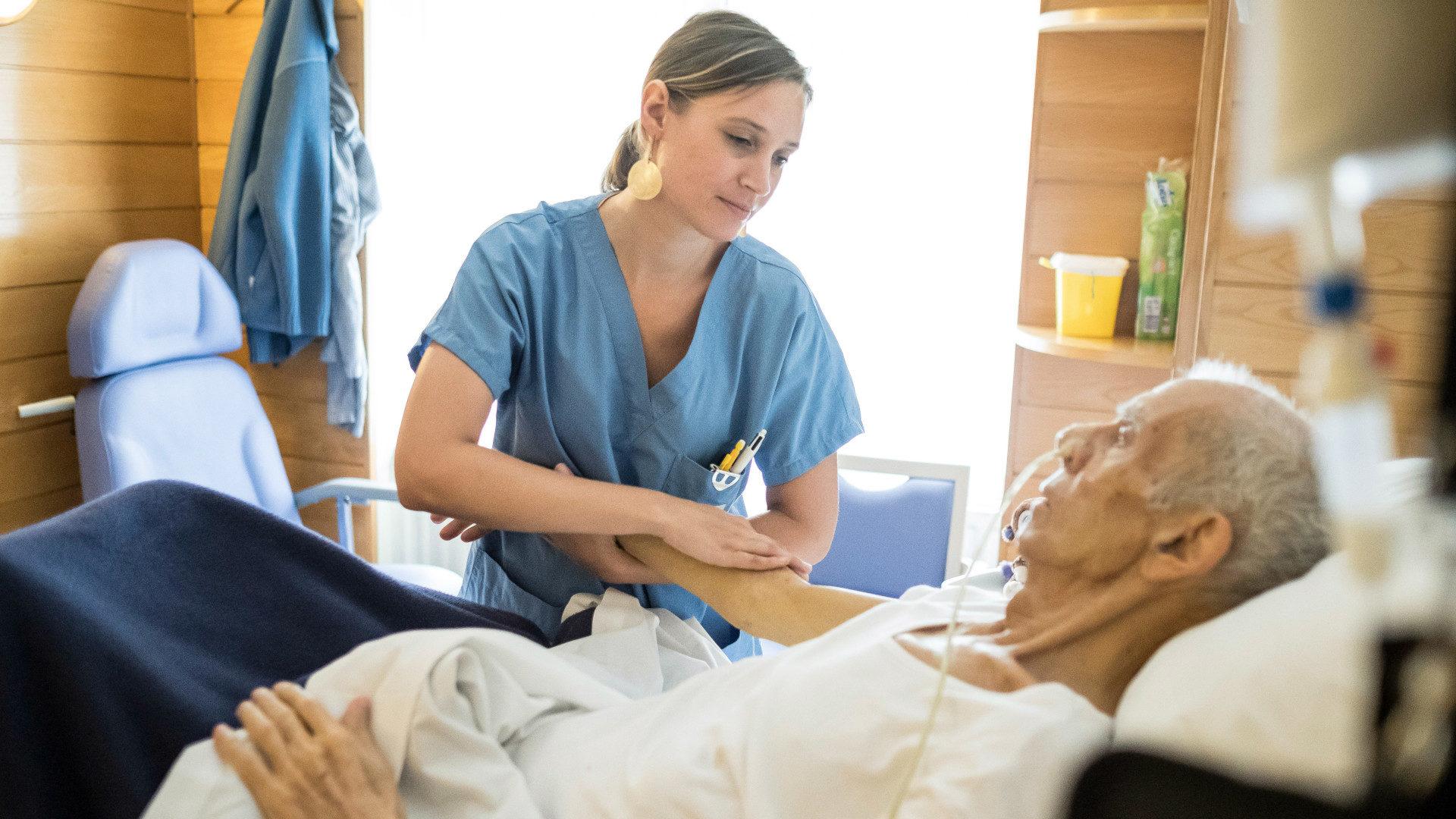 Pflegerin massiert den Arm eines bettlägerigen Mannes in einer Palliativstation | © KNA