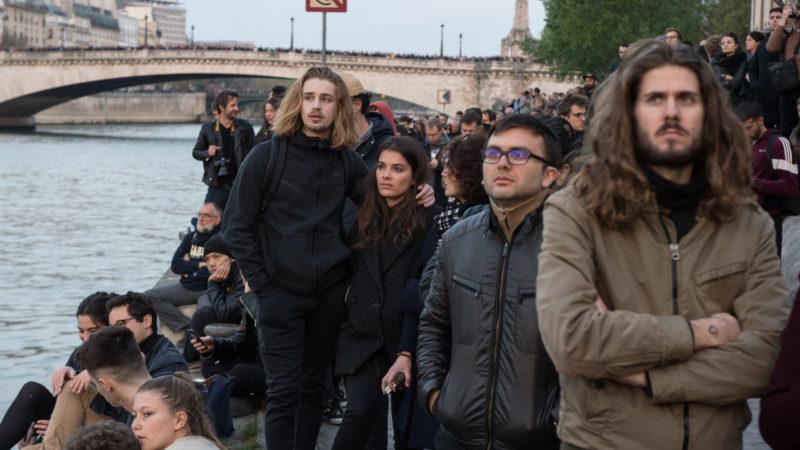 Menschen stehen und blicken auf den Brand der Kathedrale Notre-Dame. | © KNA