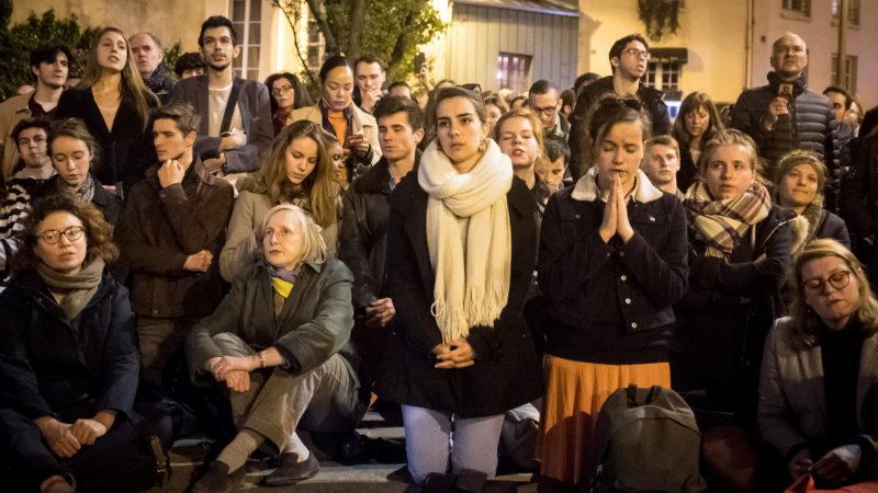 Brand von Notre-Dame Paris: Menschen sitzen und knien zusammen, manche beten. | © KNA
