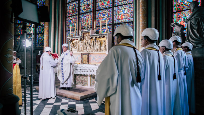 Die erste Messe nach dem Brand muss mit Schutzhelmen gefeiert werden.   © KNA