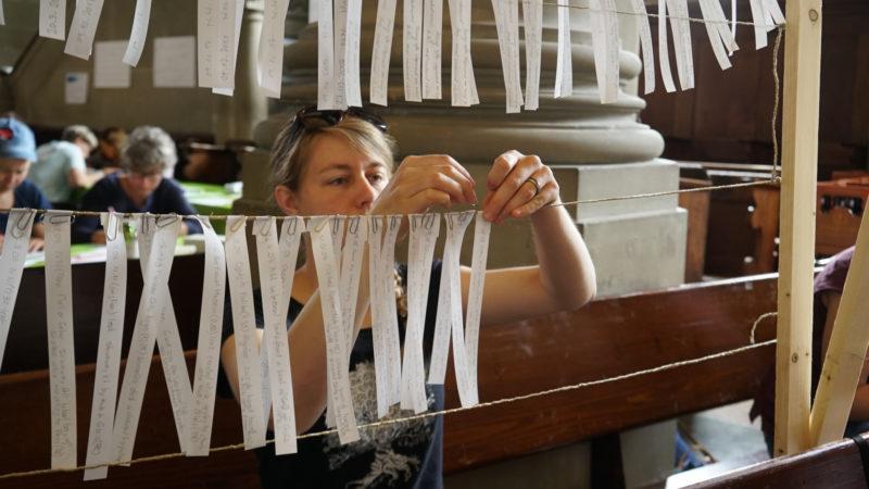 Die Namen der Flüchtlinge werden auf weisse Bänder geschrieben und aufgehängt. | © Vera Rüttimann
