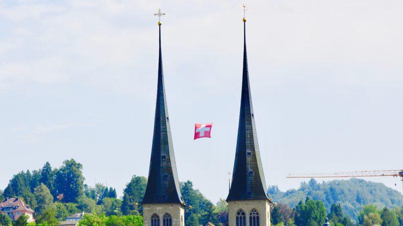 Schweizer Fahne zwischen den Türmen bei St. Leodigar im Hof |© 2017 GFX