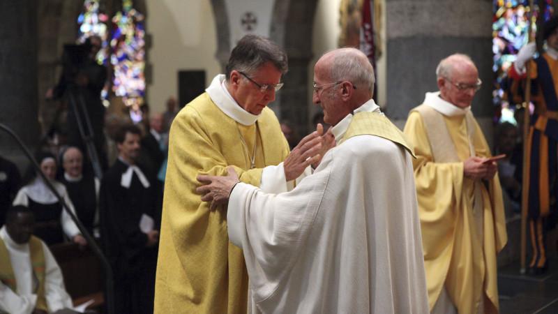 Très ému, Mgr Jean Scarcella reçoit le baiser de paix de Mgr Joseph Roduit dont il prend la succession ce jour (Photo: Bernard Hallet)