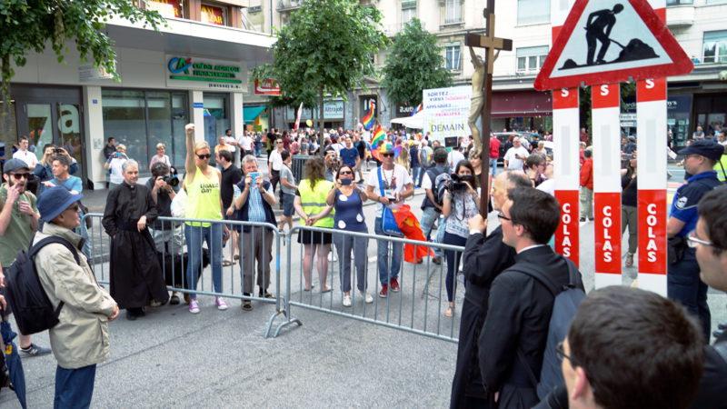 Des membres de la FSSPX et des participants à la Gay Pride, en face à face, à Fribourg (Photo: Georges Scherrer)