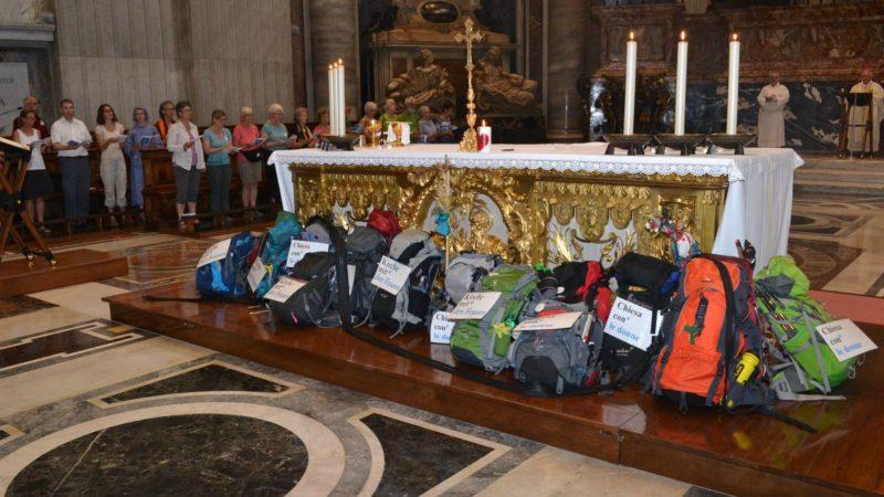"""Les sacs à dos avec les pancartes """"L'Eglise avec les femmes"""" rédigées dans les quatre langues nationales. (Photo: Sylvia Stam)"""