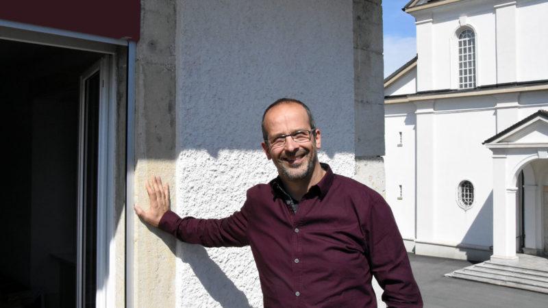 Didier Berret, un diacre responsable de paroisse qui se tient au seuil de l'Eglise. (Photo: Grégory Roth)