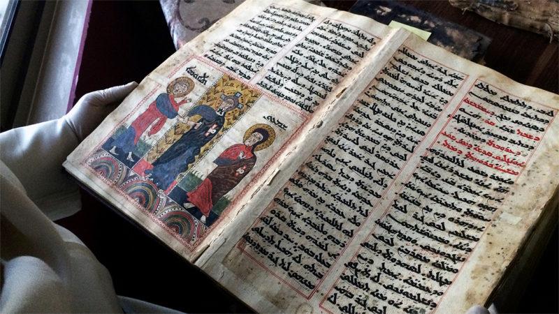Le Père Najeeb Michaeel montre un des manuscrits chrétiens qu'il a pu sauver (Photo: npr.org)