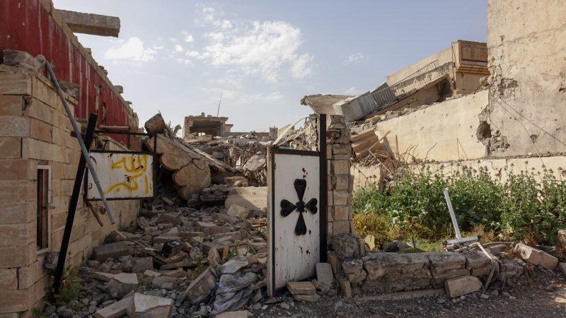 """Le village fantôme de Batnaya, dans la plaine de Ninive en Irak. A gauche de la croix chrétienne, le tag en jaune signifie """"Allah Akbar"""" (photo Maurice Page)"""